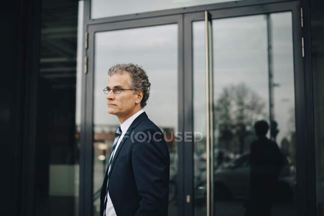 Vue latérale de l'homme d'affaires portant un costume regardant loin tout en se tenant dans la ville — Photo de stock