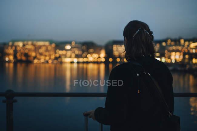 Vista general de las empresarias que miran la ciudad iluminada durante el viaje de negocios. - foto de stock