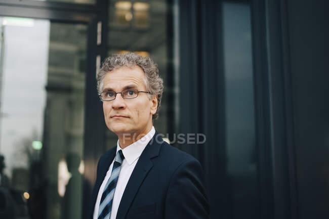 Homme d'affaires homme portant costume regardant loin tout en se tenant en ville — Photo de stock