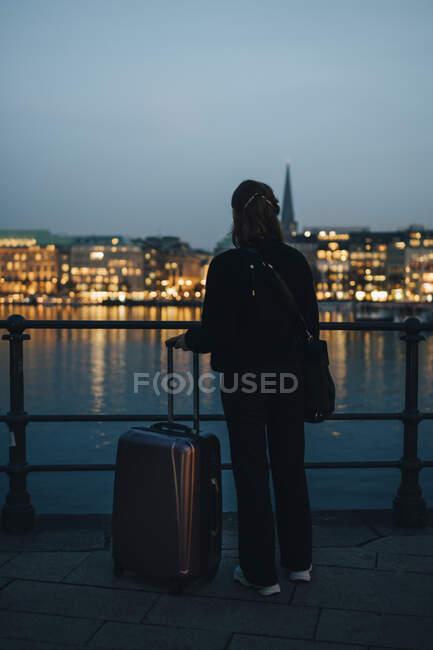 Vista posteriore della donna d'affari con bagagli guardando la città illuminata — Foto stock