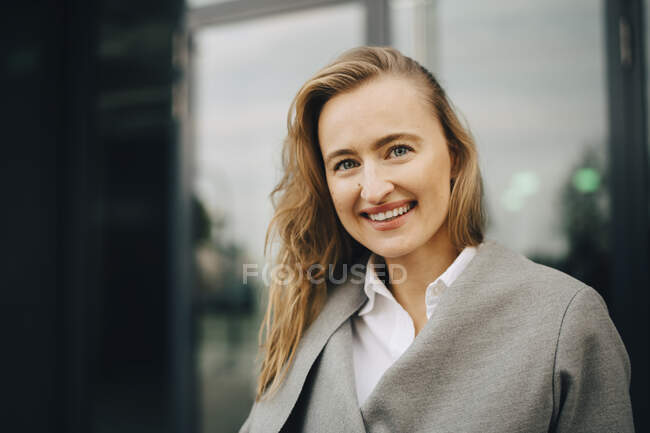 Portrait of smiling entrepreneur standing in city — Stock Photo