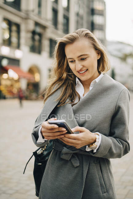 Smiling entrepreneur using smart phone while standing in city. - foto de stock