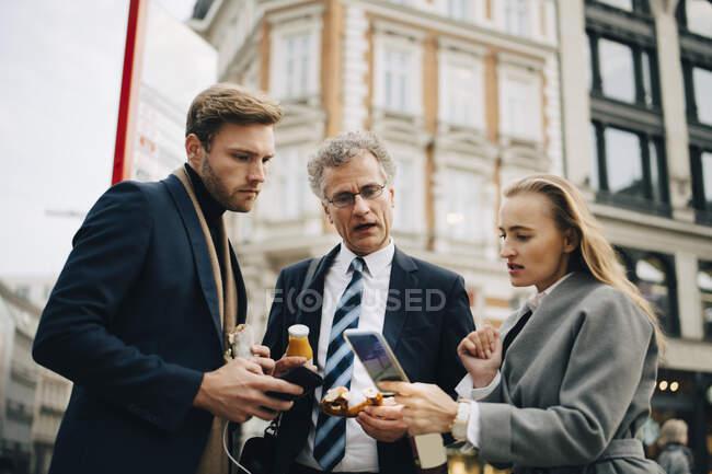 Низький кут зору професіоналів бізнесу, які дивляться на смартфон, стоячи в місті. — стокове фото