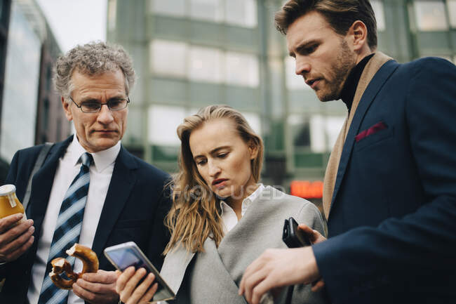 Low angle view of worried business people looking at mobile phone while standing in city — Stock Photo