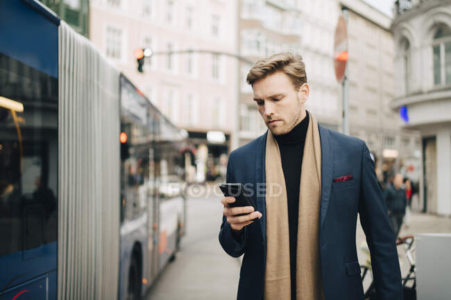 Empresaria masculina que utiliza Internet a través del teléfono móvil mientras está de pie en autobús en la ciudad. - foto de stock