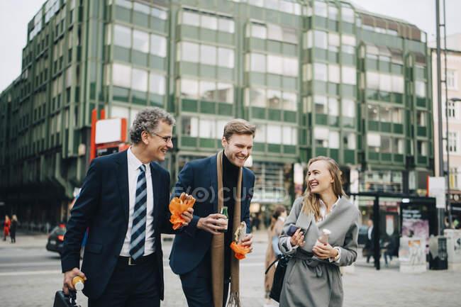 Усміхнені комерсанти розмовляють, коли тримають їжу та напої в місті. — стокове фото