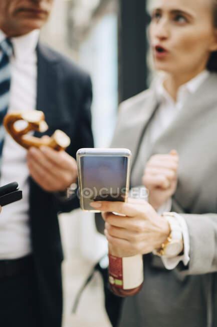 Mujer empresaria con teléfono inteligente hablando con compañeros de trabajo masculinos en la ciudad - foto de stock