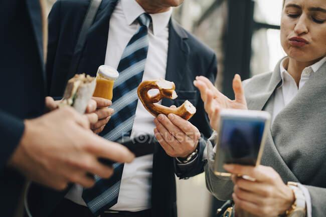 Femme d'affaires regardant le téléphone intelligent tout en étant debout par des collègues dans la ville — Photo de stock