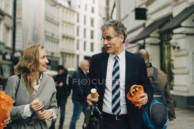 Homme d'affaires et femme d'affaires avec repas marchant en ville — Photo de stock