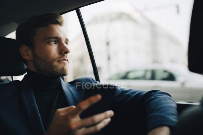 Uomo imprenditore con telefono guardando attraverso la finestra mentre seduto in taxi — Foto stock