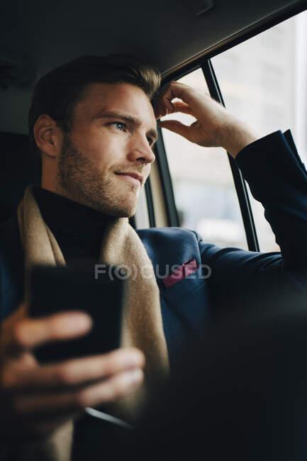 Fiducioso uomo d'affari in giacca e cravatta guardando attraverso la finestra mentre seduto in taxi — Foto stock