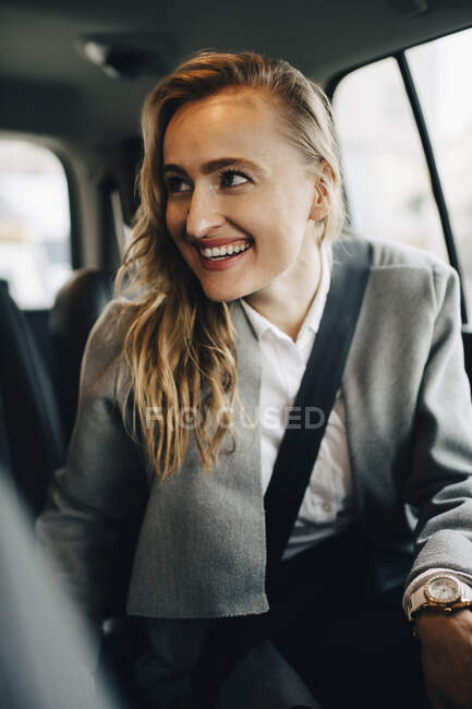 Смолящий в сторону предприниматель пристегнут ремнем безопасности в такси — стоковое фото
