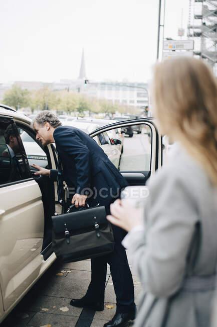 Vista lateral del hombre de negocios maduro en taxi en la ciudad. - foto de stock