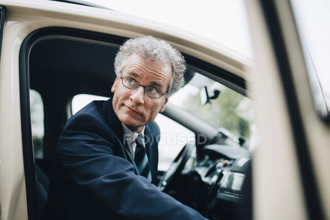 Homme entrepreneur mature sortir du taxi pendant le voyage d'affaires en ville — Photo de stock