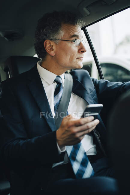 Businessman with smart phone looking through window while sitting in taxi — Stock Photo
