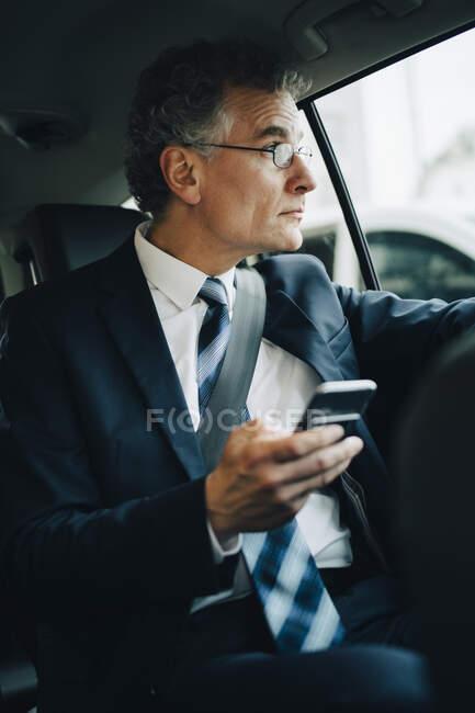 Homme d'affaires avec téléphone intelligent regardant par la fenêtre tout en étant assis dans un taxi — Photo de stock