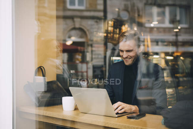 Smiling businessman using laptop in cafe seen through glass window — Stock Photo