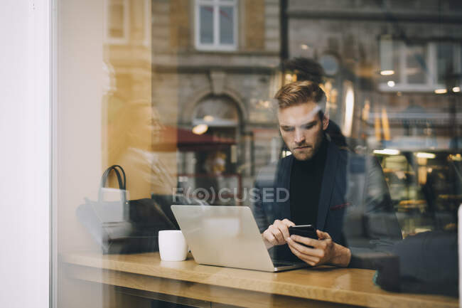 Businessman using smart phone in cafe seen through glass window — Stock Photo