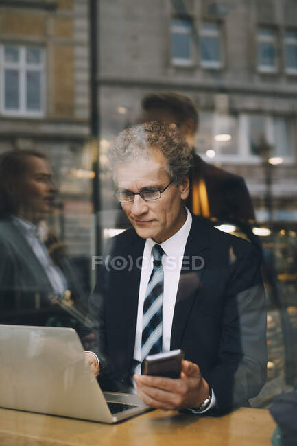 Smiling businessman with smart phone using laptop in cafe seen through glass window — Stock Photo