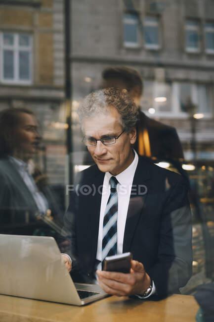 Homme d'affaires souriant avec téléphone intelligent en utilisant un ordinateur portable dans un café vu par une fenêtre en verre — Photo de stock