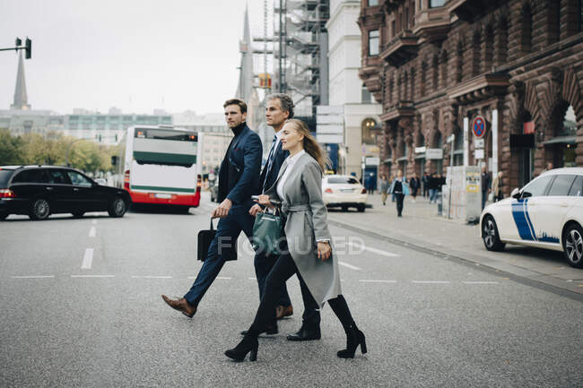 Businesswoman with male colleagues crossing road in city — Stock Photo