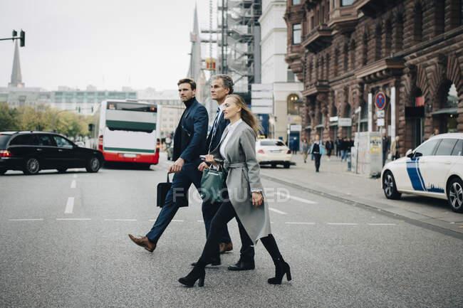 Empresarios con colegas masculinos que cruzan la carretera en la ciudad - foto de stock