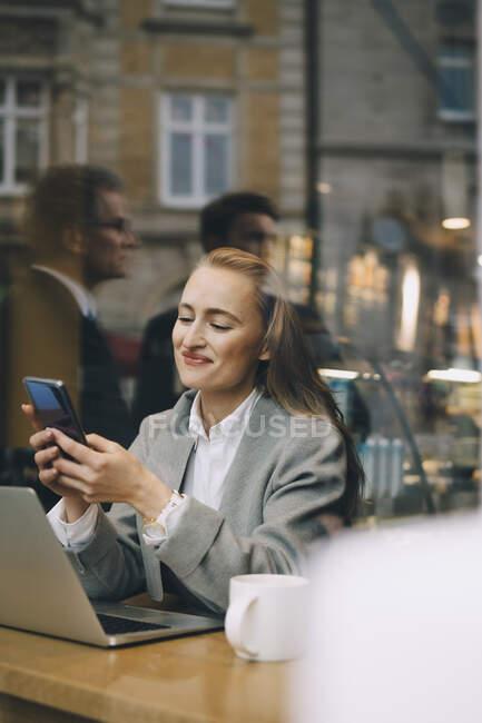 Smiling business woman using smart phone in cafe seen through glass window. - foto de stock
