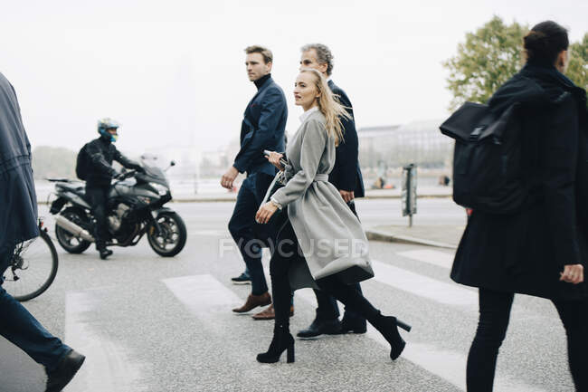 Businesswoman with male coworkers crossing road in city — Stock Photo