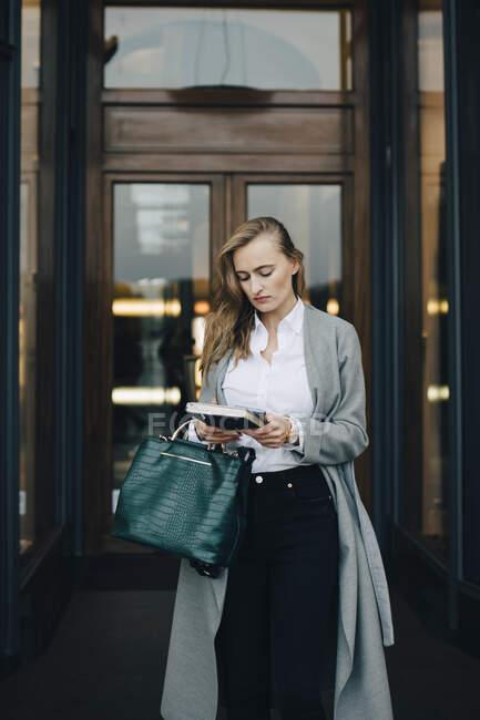 Donna d'affari con libro in piedi vicino al negozio in città — Foto stock