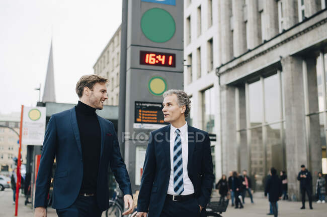 Businessman with male colleague walking in city — Stock Photo