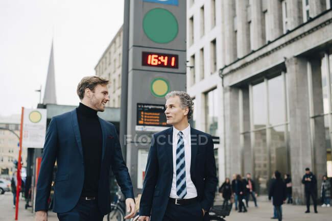 Empresario con colegas masculinos paseando por la ciudad - foto de stock