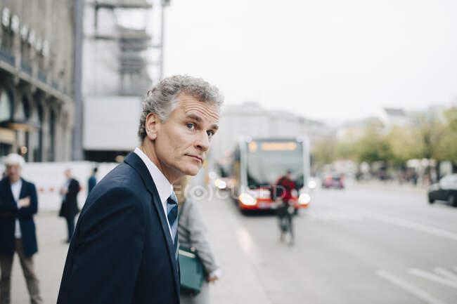 Homme d'affaires mature regardant loin tout en se tenant dans la ville — Photo de stock