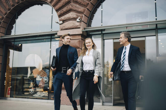 Усміхнена ділова жінка з колегами - чоловіками, які йдуть проти будівництва в місті. — стокове фото