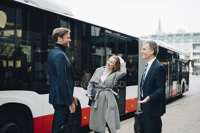 Smiling businesswoman with male coworkers standing against bus in city — Stock Photo