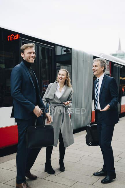 Mujer empresaria sonriente con colegas masculinos que se oponen al autobús en la ciudad - foto de stock