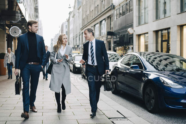 Donna d'affari con colleghi maschi che camminano sul marciapiede in città — Foto stock