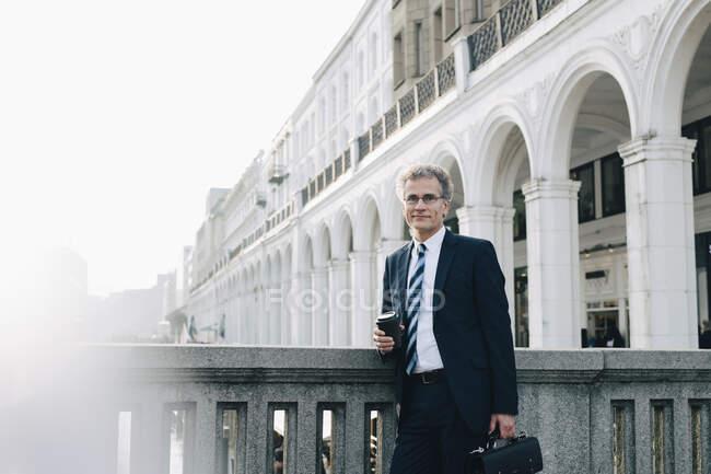 Retrato de empresario confiado con copa desechable conservando la pared en la ciudad. - foto de stock