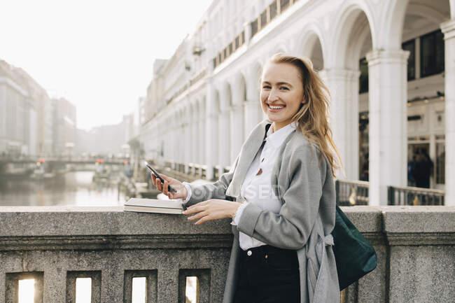 Retrato de mujer de negocios con elegante teléfono de pie conservando la pared en la ciudad. - foto de stock