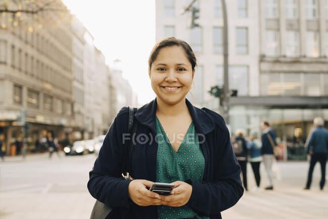 Retrato de la mujer empresaria sonriente con teléfono en la ciudad - foto de stock