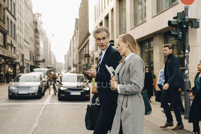 Side view of female business person with male coworker crossing road in city — Stock Photo