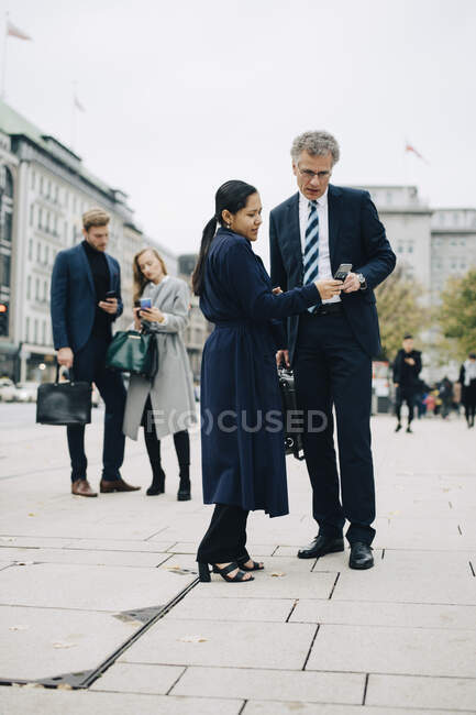 Empresarias femeninas y masculinas que utilizan teléfonos inteligentes mientras se encuentran en la calle en la ciudad. - foto de stock