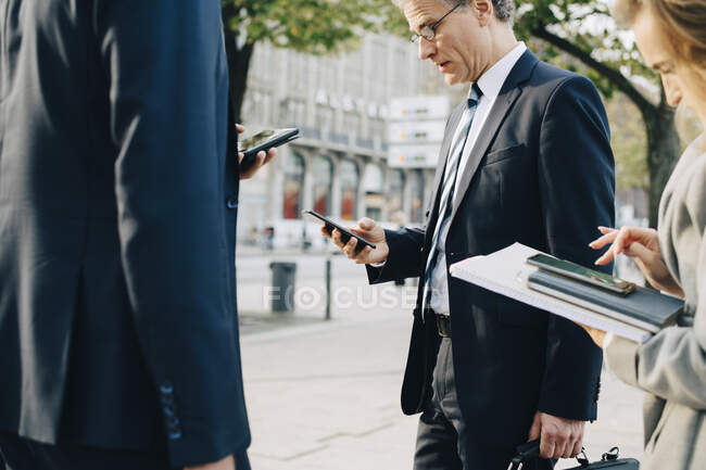 Business professionals using smart phone while standing in city — Stock Photo