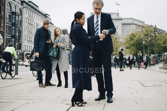 Male and female entrepreneurs using smart phone while standing on street in city — Stock Photo