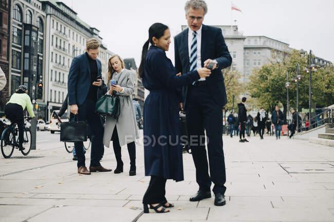 Empresarias masculinas y femeninas que utilizan teléfonos inteligentes mientras se encuentran en la calle en la ciudad. - foto de stock