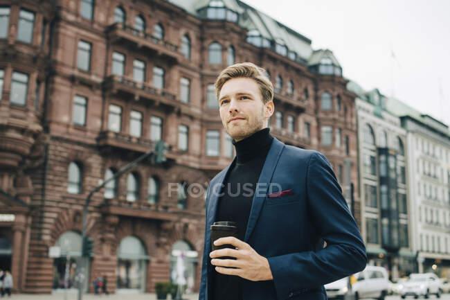 Vista basso angolo di uomo d'affari con tazza usa e getta guardando altrove mentre in piedi contro edificio in città — Foto stock