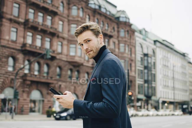 Portrait d'homme d'affaires avec téléphone intelligent debout contre le bâtiment en ville — Photo de stock
