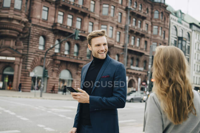 Smiling business man with phone looking at female coworker while standing in city. - foto de stock