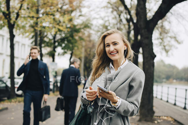 Smiling businesswoman with in-ear headphones and smart phone standing in city — Stock Photo
