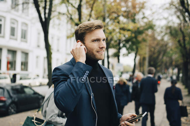 Businessman looking away while holding in-ear headphones in city — Stock Photo