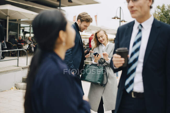 Smiling entrepreneur by male colleagues using smart phone in city. - foto de stock